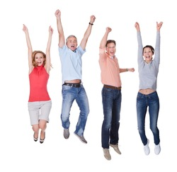 Two happy couples in casual clothing jumping in the air rejoicing with their arms raised isolated on white