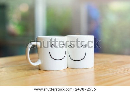 Two happy cups on the wood table, about love concept #249872536