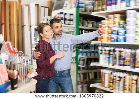 Two happy designers are choosing paint for redecorate room in the store