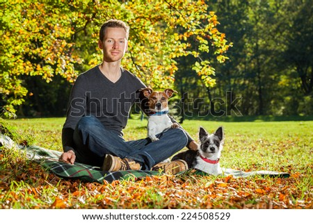 two happy dogs with owner sitting on grass in the park