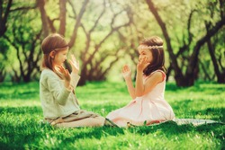 two happy dressy girls clapping and playing on spring walk, outdoor activities, friendship concept