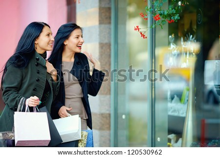 two happy elegant women looking in shop window