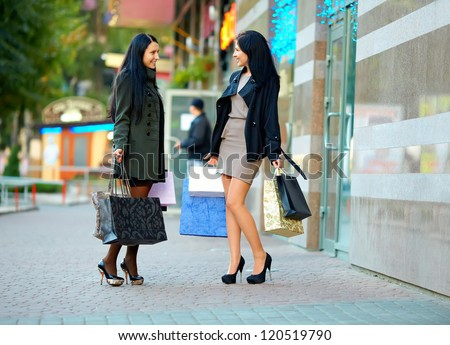 two happy elegant women shopping in the city