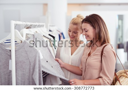Two Happy Female Best Friends Looking at the Quality of a Gray Shirt Hanging on a Rail inside the Clothing Store.