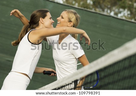 Two happy female tennis player embrace after a winning game