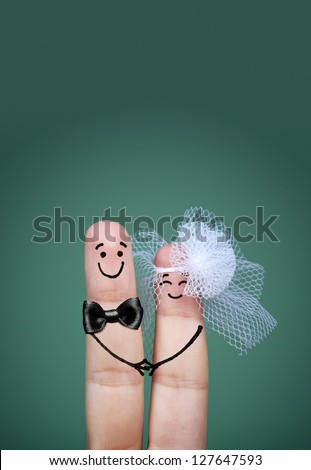 Two happy fingers decorated as bride and groom with veil and bow tie #127647593