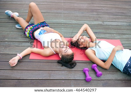 Two happy fit young women friends lying down tired after workout exercising in a park. Active healthy lifestyle concept #464540297