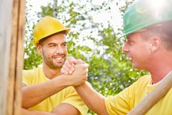 Two happy fitters or construction workers shake hands while building a house