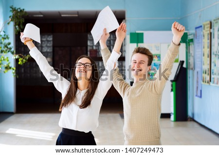 Two happy friends happy after researching their checked exams, raising hands up and expressing amusement of getting excellent grades for their work #1407249473