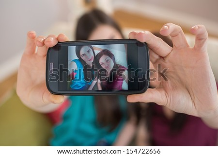 Two happy friends on the couch taking a selfie with smartphone at home in the living room
