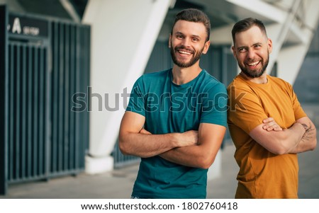 Two happy friends or brothers in colorful t-shirts are standing back to back with crossed arms outdoors Foto stock ©