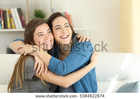 Stock Photo Two happy friends or sisters hugging sitting on a couch in the living room at home