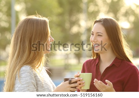 Two happy friends talking holding tea mug outdoors in a park with a green background at sunset with a warm back light