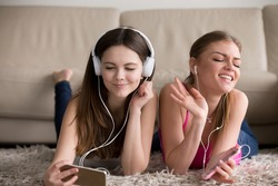 Two happy girlfriends in stylish white earphones and headphones lying on soft carpet on floor, sisters enjoying their favorite music tunes on modern smartphones. Siblings having fun at home concept.