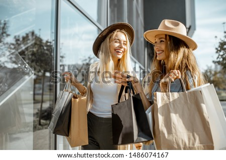 Two happy girlfriends looking on the shopwindow while standing with shopping bags near the mall