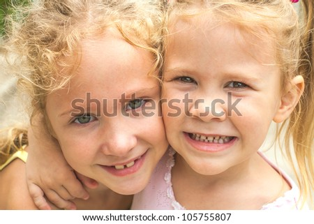 two happy girls are embracing - stock photo