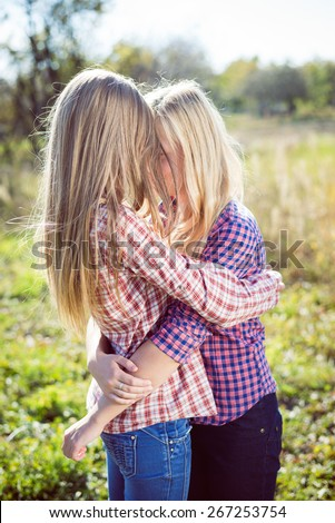 Two happy girls embracing together on bright sunny day outdoors background