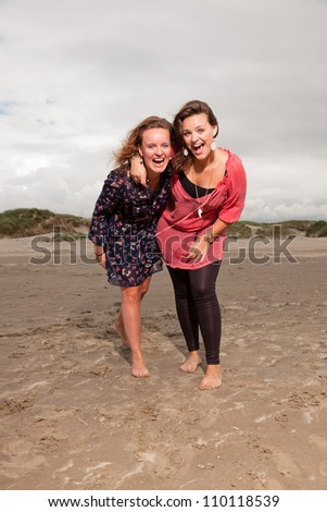 Two happy girls enjoying outdoor nature near the beach. Red and brown hair. Cloudy sky.