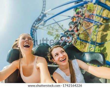 Two happy girls having fun on rollercoaster Foto stock ©