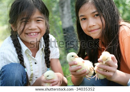 Two happy girls holding their pet chicks
