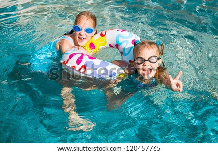 two happy  girls  in the pool  with rubber ring - stock photo