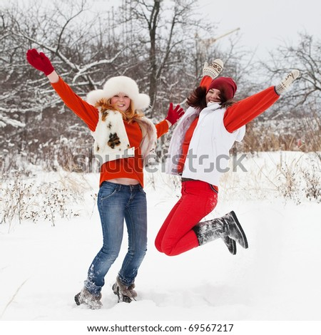 Two happy girls is jumping at  winter park