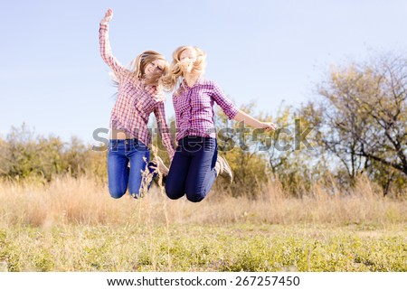 Two happy girls jumping high on empty sunny day outdoors field
