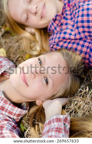 Two happy girls lying head to head on outdoors, closeup portrait