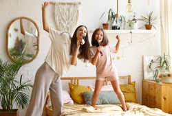 Two happy girls, overjoyed younger and older sister singing with hairbrush, looking at camera and smiling while spending time together at home, mom and cute little daughter having fun in bedroom