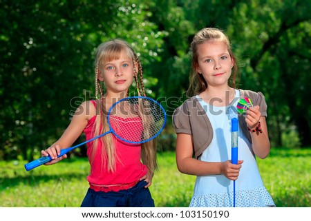 Two happy girls playing tennis outdoors.