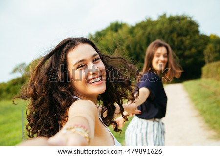 Two happy girls running in nature holding hands. Point Of View Shot.