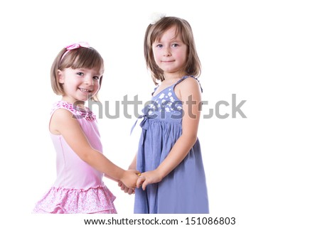 Two happy girls sisters holding by hands isolated on white