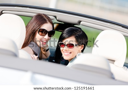 Two happy girls sitting in the car glance back and have fun while having little car trip