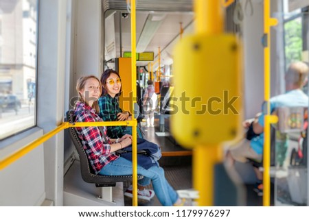 Two happy girls smiling to the camera inside the tram