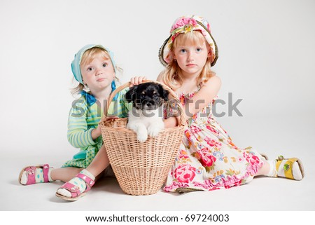 two happy girls with puppy in basket