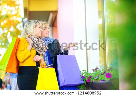 two happy girls with shopping bags show hand and look at the shop window