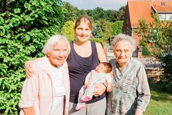 Two happy great grandmothers with granddaughter and newborn great granddaughter baby outdoors - Kempen, Germany