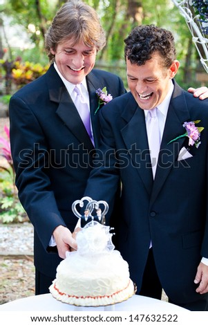 Two happy grooms cutting the cake at their wedding.