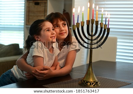 Two happy Jewish sisters looking at a beautiful menorah candelabra glowing on the eight day of Hanukkah Jewish holiday. stock photo