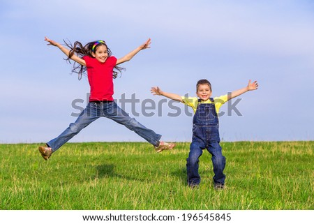 Two happy jumping kids on green field, outdoors - stock photo