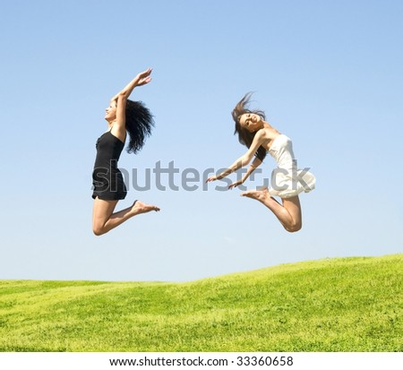 two happy jumping woman on a sky background