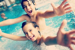 Two happy kids having fun on summer pool (colorized effect)