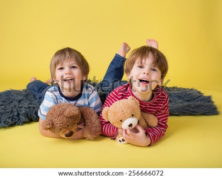 Two happy kids hugging stuffed toy animals, laughing. Siblings, brothers or friends.