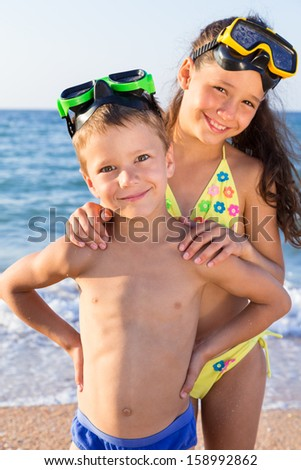 Two happy kids in diving masks standing together on the beach