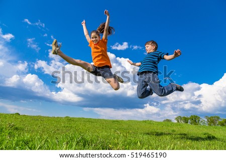 Two happy kids jumping on green hills against blue sky