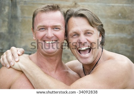 stock photo : Two happy laughing gay men cuddle up together.