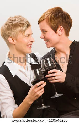 Two happy lesbians and a glass of red wine, vertical format