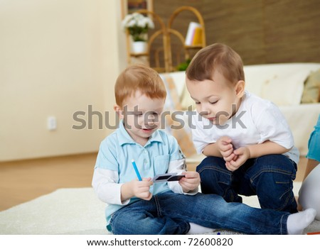 two happy little boys playing together at home on the floor