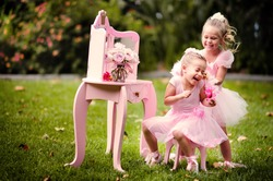 two happy little girl wearing in princess costumes have a fun in a beautiful garden
