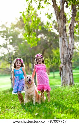 Two happy little girls and a golden retriever in the park